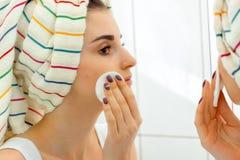 有一块毛巾的一个女孩在他的头抹面孔构成与棉花盘 库存照片