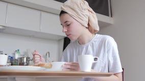 有一块毛巾的一少女在她的头食用早餐,吃早晨谷物,在阵雨以后,看窗口 影视素材