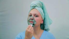 有一块毛巾的一年轻女人在她的头应用在她的面孔的泥面具与刷子 查看照相机 股票录像