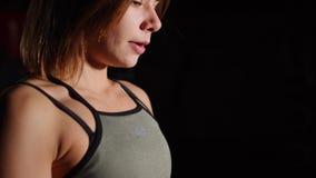 有一块毛巾的华美的少妇在她的从一个瓶的脖子饮用水在健身房 影视素材