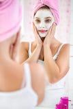 有一块毛巾的女孩在她的顶头和化妆面具 免版税图库摄影