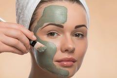 有一块毛巾的温泉女孩在她的应用脸面护理的头 图库摄影
