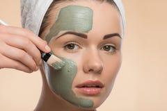 有一块毛巾的温泉女孩在她的应用脸面护理的头 免版税库存照片