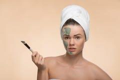 有一块毛巾的温泉女孩在她的应用脸面护理的头 库存照片