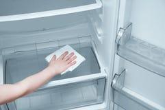 有一块白色旧布的女孩手洗涤冰箱 免版税库存照片