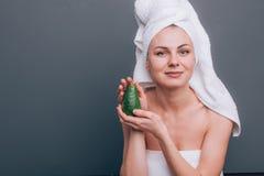 有一块白色毛巾的女孩在她的有一个滋补绿色面具的头在她的面孔和一个鲕梨在她的手上在绿色背景机智 免版税图库摄影