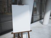 有一块空白的白色帆布的木画架在办公楼附近 免版税库存照片