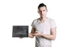 有一块空的灰色匾的一个年轻英俊的人,对匾的点 署名的,文本地方 水平的框架 库存照片