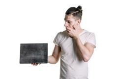 有一块空的灰色匾的一个年轻英俊的人,看充满惊讶的板材 署名的,文本地方 水平的fram 库存图片