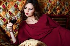 有一块红葡萄酒玻璃的妇女在一个壮观的沙发 图库摄影
