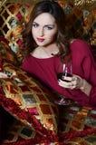 有一块红葡萄酒玻璃的妇女在一个壮观的沙发 免版税库存照片