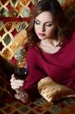 有一块红葡萄酒玻璃的妇女在一个壮观的沙发 库存照片