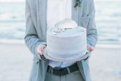 有一块装饰的婚宴喜饼的新郎在海滨 库存照片