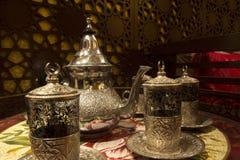 有一块铜玻璃的摩洛哥茶壶在盘子 免版税库存照片