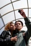 有一块黑玻璃的一个美丽的非裔美国人的女孩在她的手上按了她的面颊给有行动照相机和w的欧洲人 库存图片