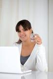 有一块水玻璃的少妇在膝上型计算机前面 图库摄影