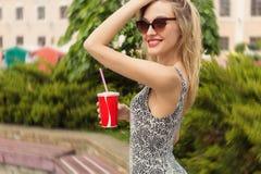 有一块玻璃的美丽的性感的逗人喜爱的愉快的微笑的女孩在他的在太阳镜的手上喝焦炭的在一晴朗的热的天 免版税库存照片