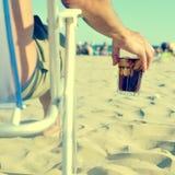 有一块玻璃的年轻人与在海滩的可乐饮料,与filt 库存照片