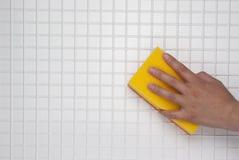 有一块黄色海绵的手 免版税图库摄影