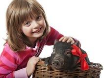 有一头小的黑色猪的一个小女孩 免版税图库摄影