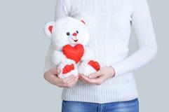 有一头毛皮玩具熊的女孩在她的手上 库存图片