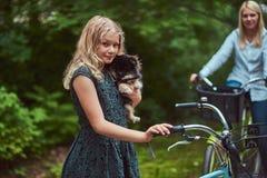 有一头金发的母亲的画象和女儿在自行车乘坐与他们逗人喜爱的小的波美丝毛狗狗在公园 免版税图库摄影