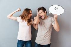有一对年轻愤怒的夫妇的画象论据 图库摄影