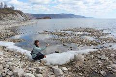 有一小块冰的妇女在贝加尔湖的一只手上 免版税库存图片