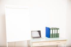 有一幅空白的活动挂图的空的办公室 免版税库存照片