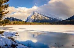 有一座参天的山的冻湖在日落的背景中 库存图片