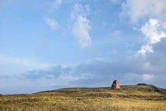 有一座古墓的草原,在破晓的剧烈的蓝天,中国 库存图片