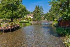 有一座步行桥的小河在有蓝色s的一个绿色公园 库存图片