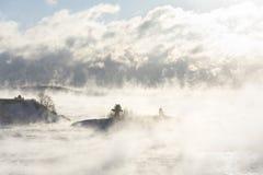 有一座灯塔的海岛在薄雾 库存图片