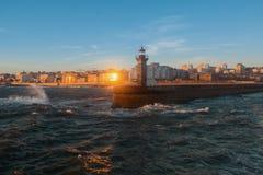 有一座灯塔的码头在日落期间的海洋海浪 免版税库存图片