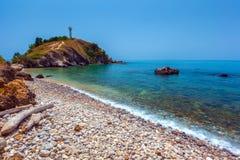 有一座灯塔的Pebble海滩在i的最南端的部分 免版税库存照片