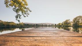 有一座老木栈桥的江边 图库摄影