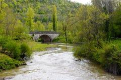 有一座老桥梁的河在山 免版税库存照片