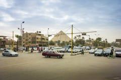 有一座金字塔的在距离,开罗,埃及繁忙的交叉点 免版税库存图片