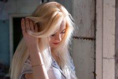 有一张俏丽的面孔的美丽的年轻白肤金发的女孩和美好眼睛微笑 一名妇女的画象有长的头发和惊奇的看 免版税库存照片
