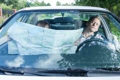 有一张地图的妇女在汽车 免版税库存图片