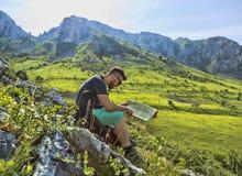 有一张地图的远足者在山 免版税库存照片