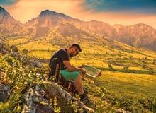 有一张地图的远足者在迷雾山脉 免版税库存照片