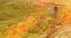 有一张地图的远足者妇女在山 库存照片