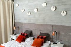 有一张大床的卧室,橙色枕头连续安排了,墙壁用灰色材料、可看见的桌和床头灯盖了 免版税库存照片