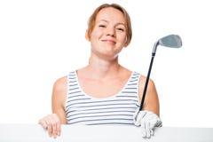 有一张海报的高尔夫球运动员在手上微笑和摆在反对白色的 免版税库存图片
