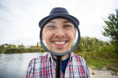 有一张滑稽的面孔的一个快乐的年轻人拿着一个放大镜 免版税库存图片