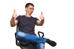 有一张滑稽的面孔的正面年轻白种人人,坐投入他的脚的椅子在喂 免版税图库摄影