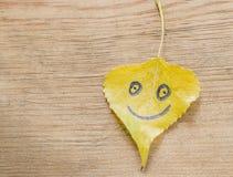 有一张滑稽的面孔的黄色叶子在与镇压的老木背景 免版税库存照片