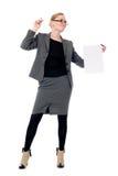 有一张空白的纸片的不快乐的女商人 免版税库存图片