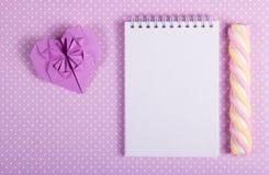 有一张空白页和棍子蛋白软糖的华伦泰origami开放笔记本在圆点背景  库存照片